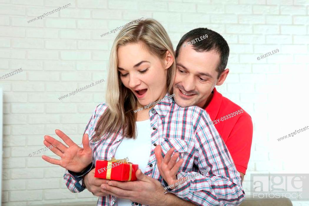 Stock Photo: valentine's day or christmas concept - young woman opening gift from her boyfriend.