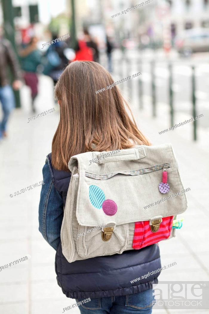 Stock Photo: Rear view of a schoolgirl walking on footpath.