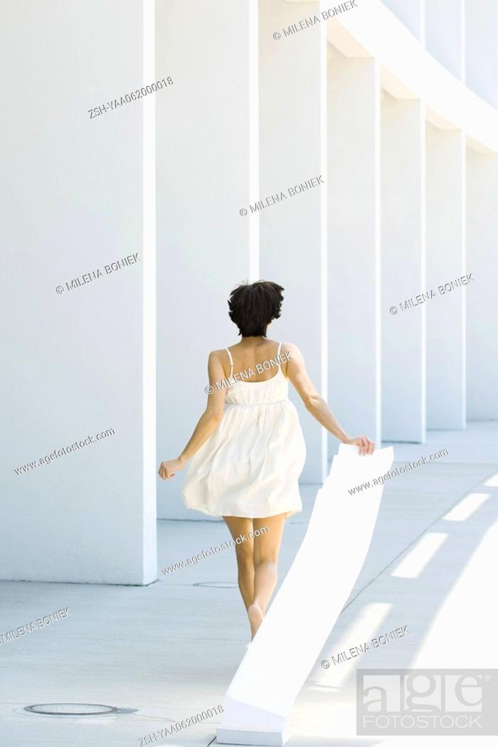 Stock Photo: Woman in sundress running outdoors, pulling paper behind her, rear view.