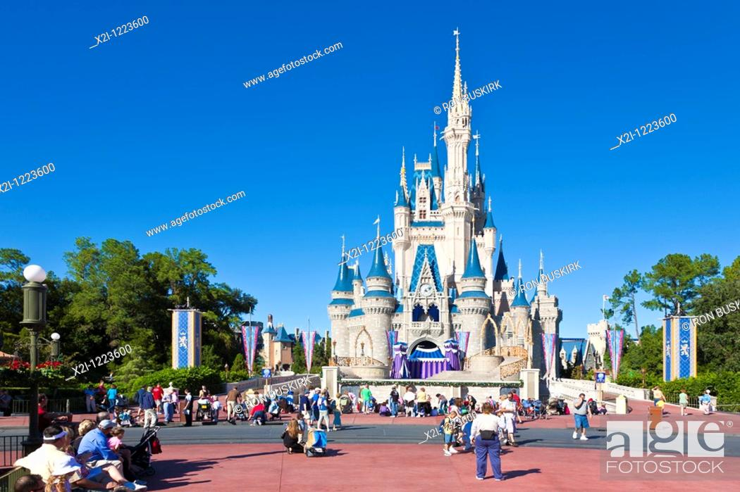 Stock Photo: Kissimmee, FL - Nov 2009 - Park guests pose for photos in front of Cinderella's Castle in Walt Disney's Magic Kingdom theme park.