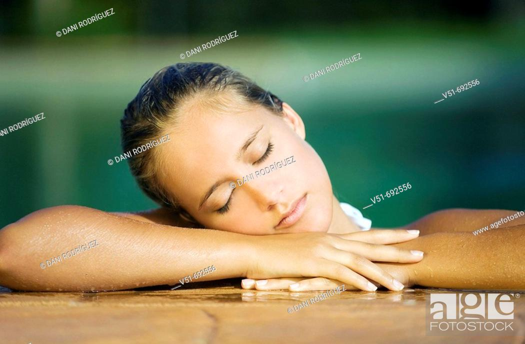 Stock Photo: Woman resting on a pool's deck.