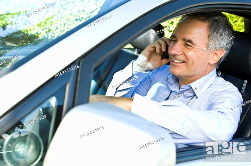 Stock Photo: Man sitting in a car and talking on a mobile phone.