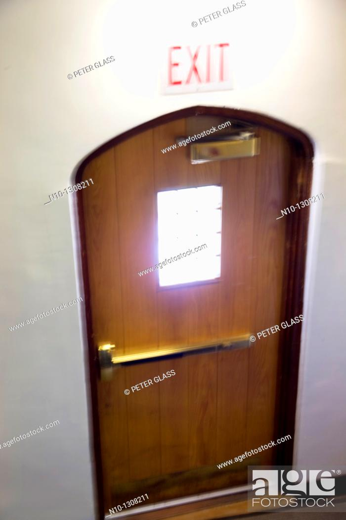 Stock Photo: Wooden door with an 'exit' sign above it.