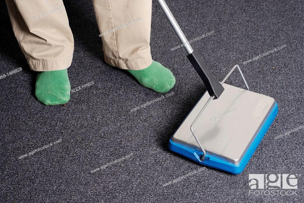 Stock Photo: An environmentally friendly man uses a contemporary carpet sweeper to clean without using any electricity.