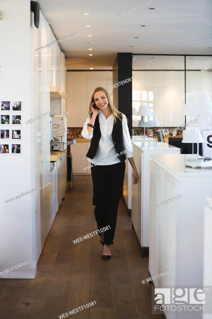 Stock Photo: Business woman in office using mobile phone.