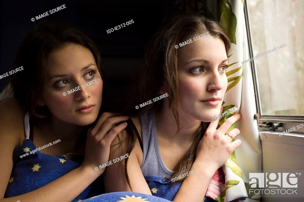 Stock Photo: Two teenage girls looking out of a window.
