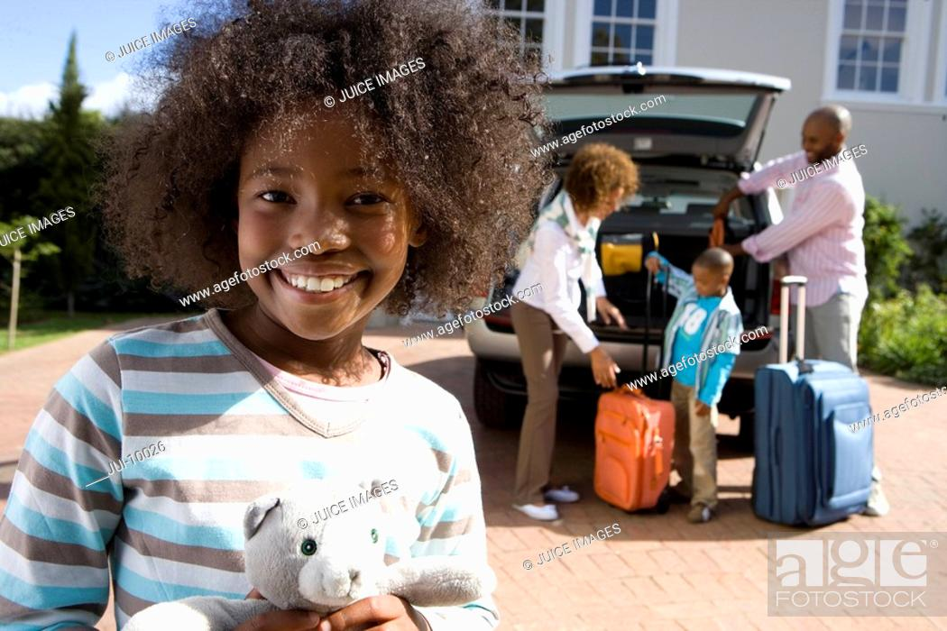 Stock Photo: Girl 8-10 holding toy in driveway, family by car in background, smiling, portrait.