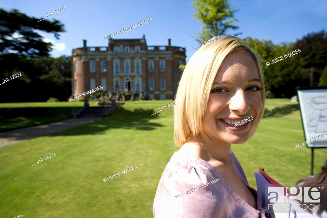 Stock Photo: Businesswoman in training course by manor house, smiling, portrait.