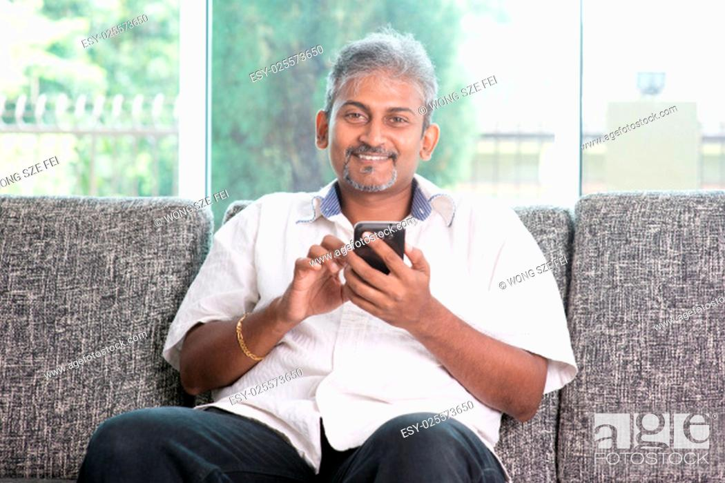 Stock Photo: Smartphone social network concept. Indian mature guy using mobile phone. Asian man relaxed and sitting on sofa indoor.