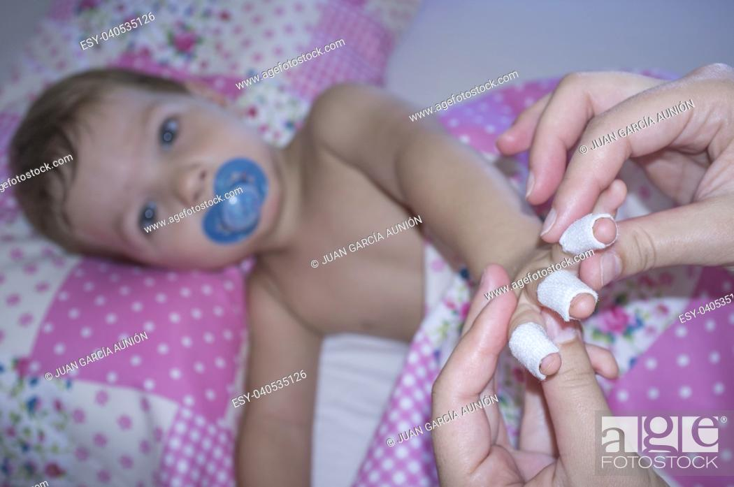 Stock Photo: Baby boy shows his bandaged fingers before suffering a domestic accident. Domestic accidents concept.