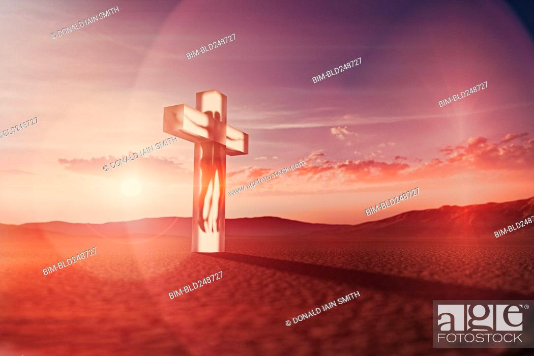 Stock Photo: Person in suspended animation inside crucifix in desert.