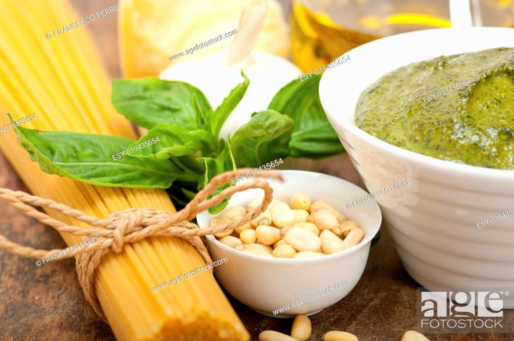 Photo de stock: Italian traditional basil pesto pasta ingredients parmesan cheese pine nuts extra virgin olive oil garlic on a rustic table.