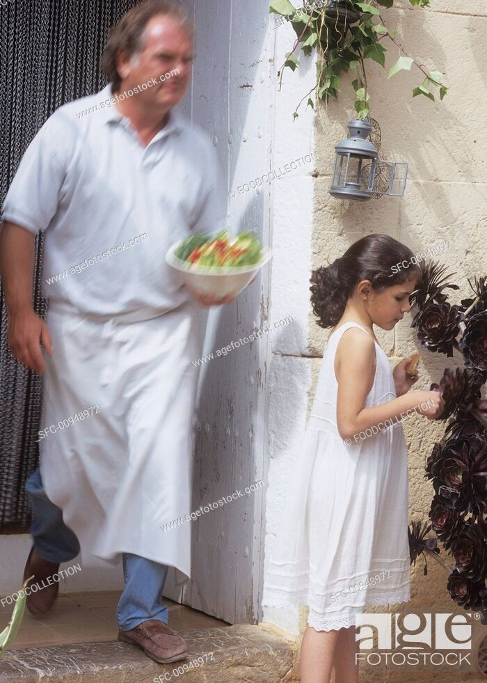 Stock Photo: Chef serving salad outside, girl beside container plant.