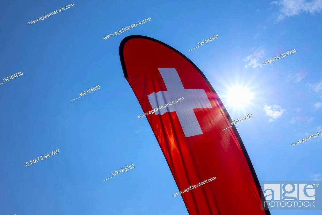 Stock Photo: Swiss Banner Flag Against Blue Sky and Sun in Switzerland.