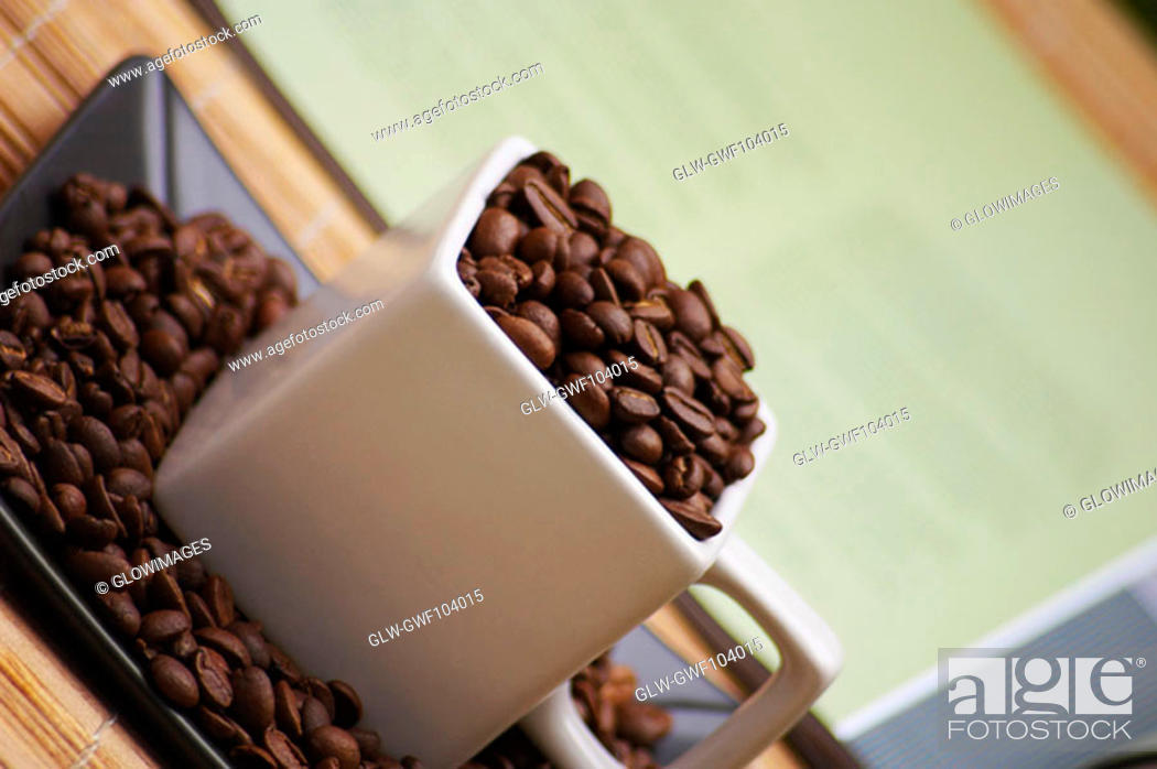 Stock Photo: High angle view of coffee beans in a cup.