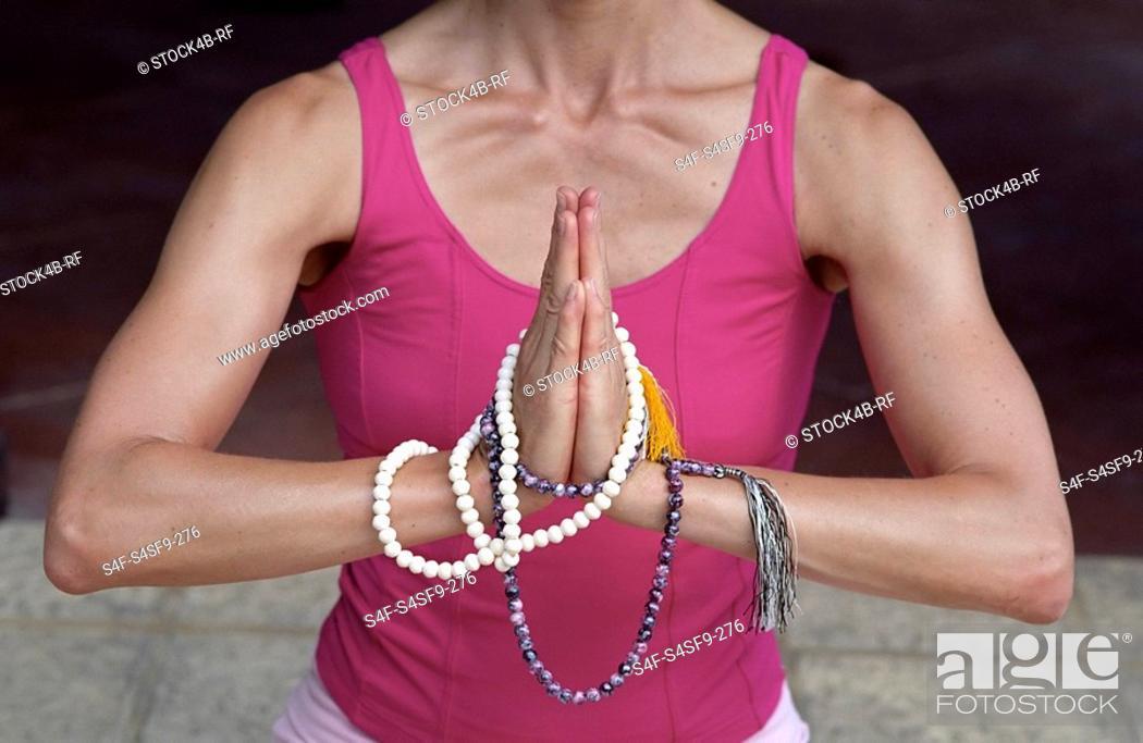 Stock Photo: Woman with Praying-Pearls around her Hands - Buddhism - Posture - Meditation.