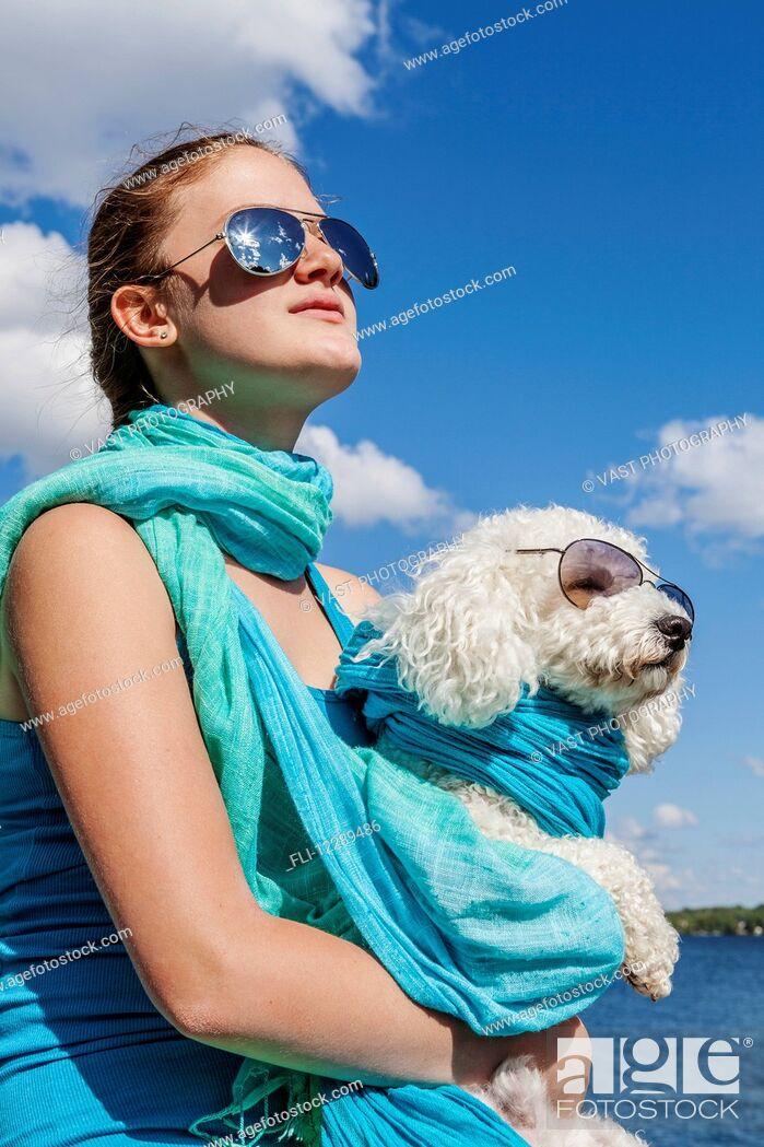 Stock Photo: Girl and her dog wearing matching sunglasses; Balsam Lake, Ontario, Canada.