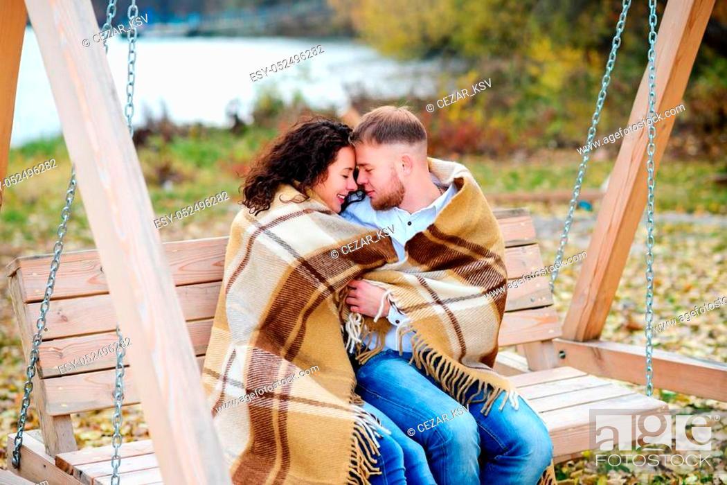 Stock Photo: Amorous couple on romantic date on swings outdoor, autumn.