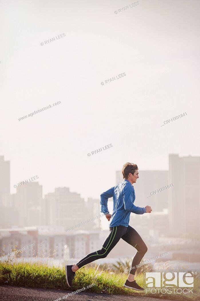 Stock Photo: Male runner running on sunny urban city street.