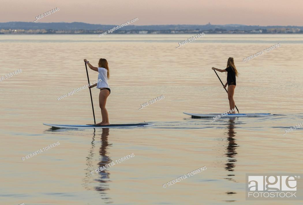 Stock Photo: Two people practicing paddle surf at Alcanda at sunset, Alcudia, Majorca, Spain.