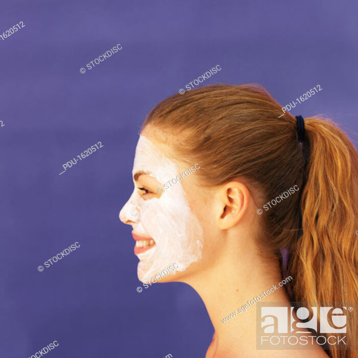 Stock Photo: Side view of young woman wearing face mask.