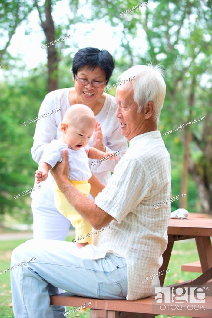 Stock Photo: chinese grandfather and grandmother playing with baby grandson at outdoor..
