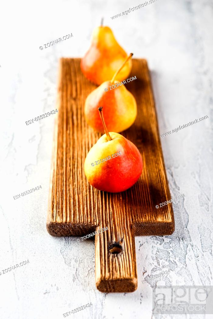 Stock Photo: Fresh bio yellow and red pears on wooden cutting board on the grey background.