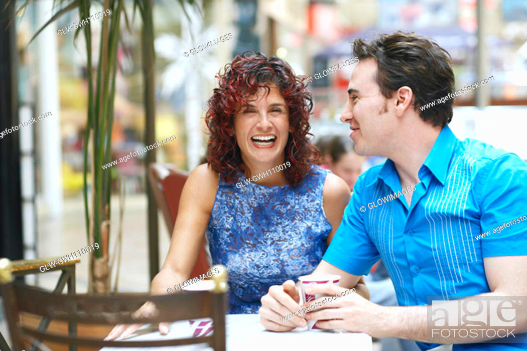 Stock Photo: Mature woman and a mid adult man sitting in a cafe.