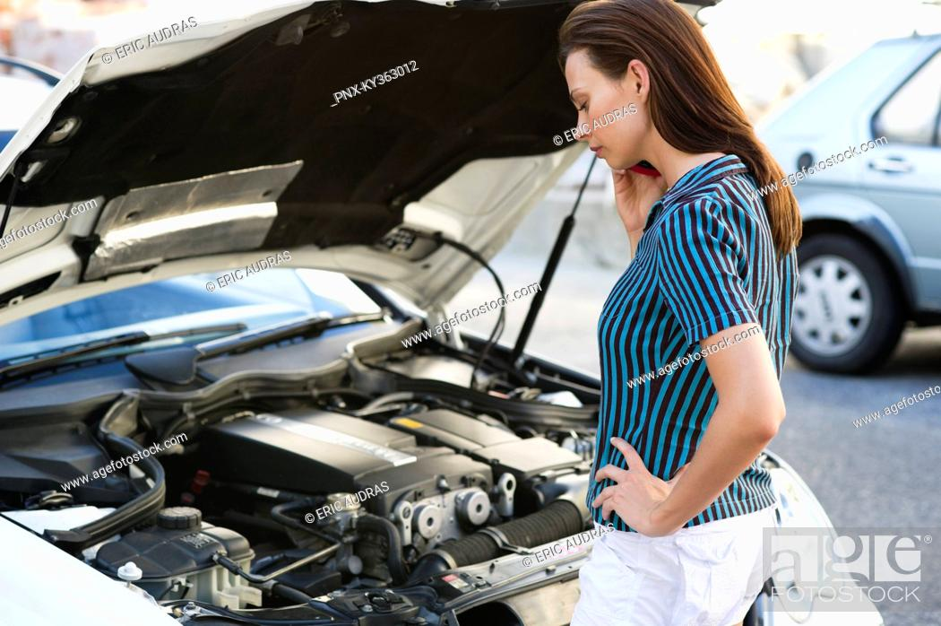 Stock Photo: Young woman talking over phone and standing by the broken car.