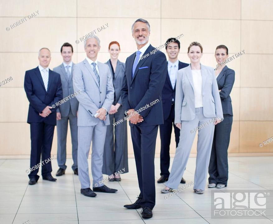 Stock Photo: Portrait of smiling business people at bottom of escalator.