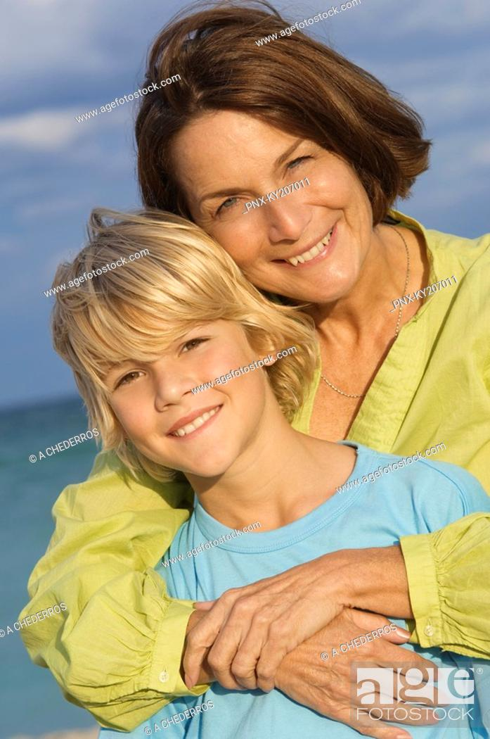 Stock Photo: Woman hugging her grandson from behind on the beach.
