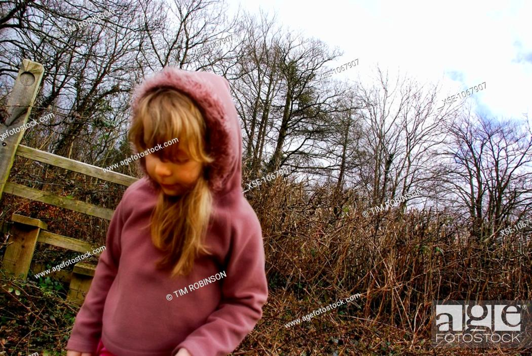 Stock Photo: 6 year girl looking downwards in rural winter scene.