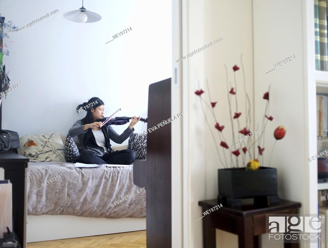 Stock Photo: young asian girl playing the violin in her bedroom in Madrid (Spain).