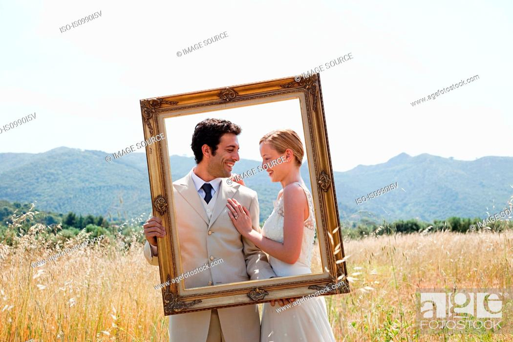 Stock Photo: Newlyweds holding vintage picture frame.