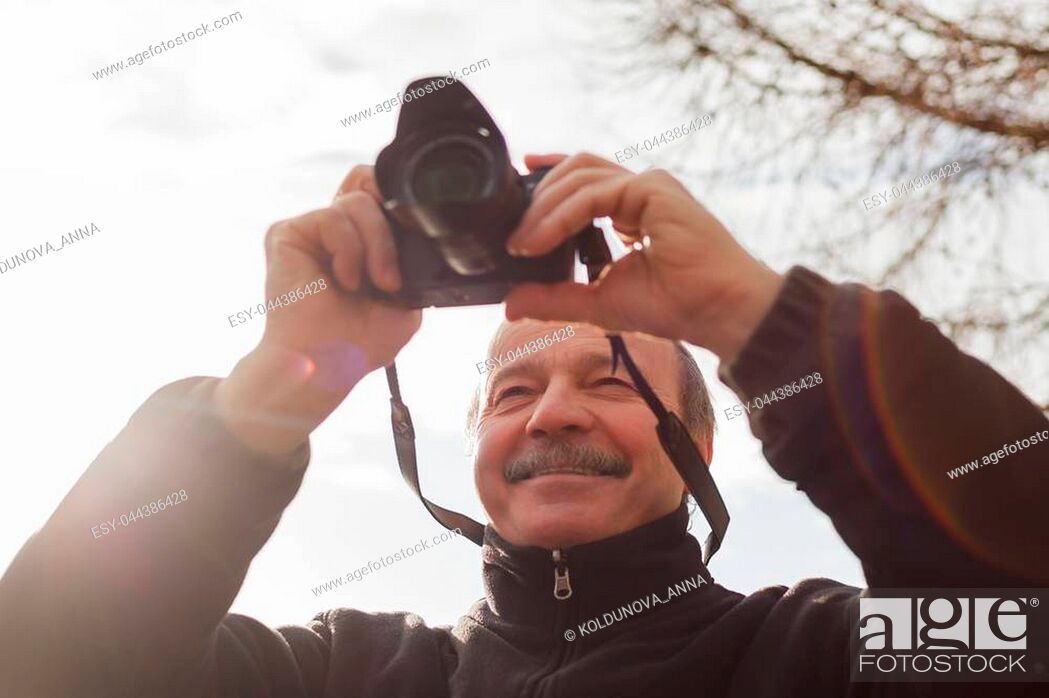 Stock Photo: An elderly man with a mirrorless camera chooses a frame on nature.