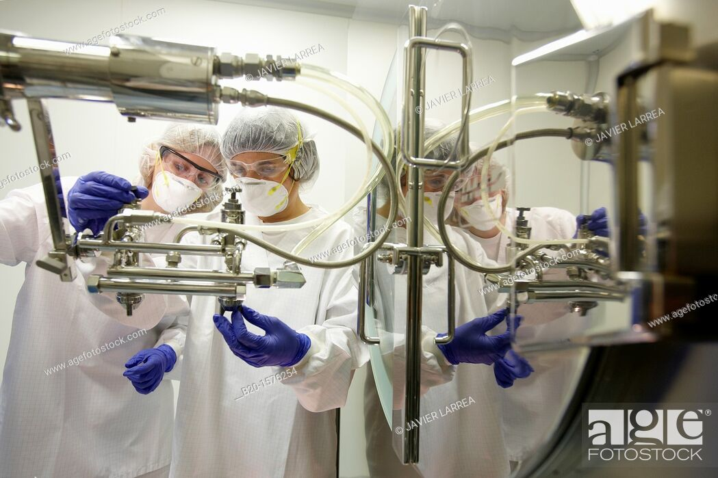 Stock Photo: Technicians performing maintenance functions on a solid coating machine, Clean room, Pharmaceutical plant, Drug manufacturing plant, Research Center, Pharmacy.