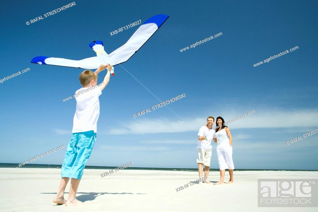 Stock Photo: family playing with kite on beach.