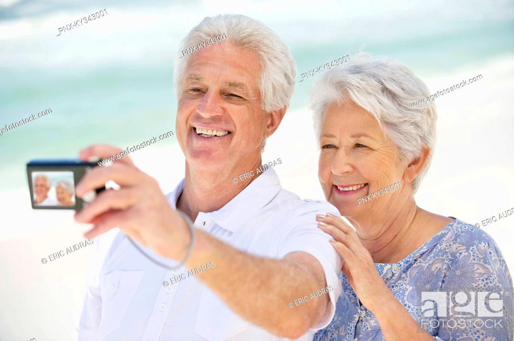 Stock Photo: Happy senior couple taking a picture of themselves with a digital camera.
