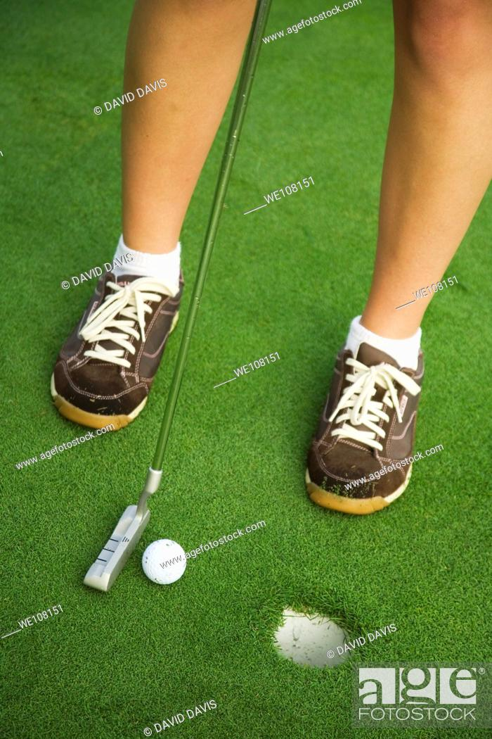 Stock Photo: Woman in her mid 20s playing golf.