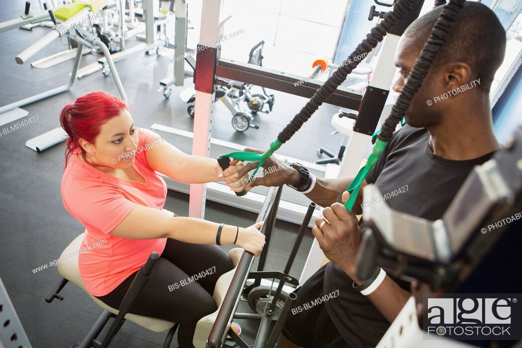 Imagen: Disabled woman doing physical therapy with trainer.