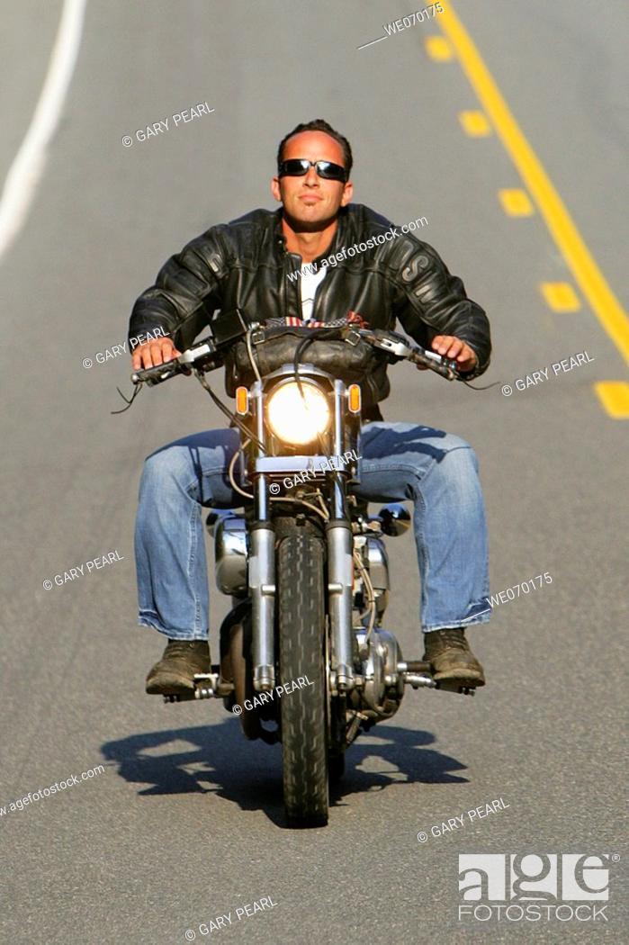 Stock Photo: Man riding his Harley Davidson Motorcycle.