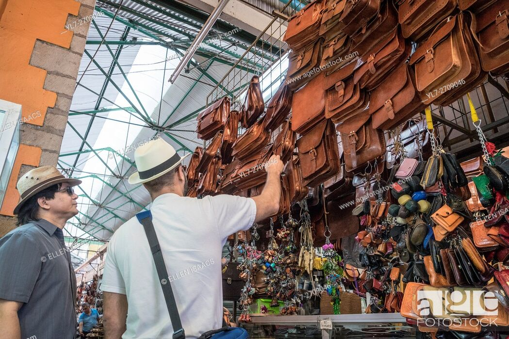 Stock Photo: Two men shopping for leather bags at a stall in the Benito Juarez Market in Oaxaca Mexico.