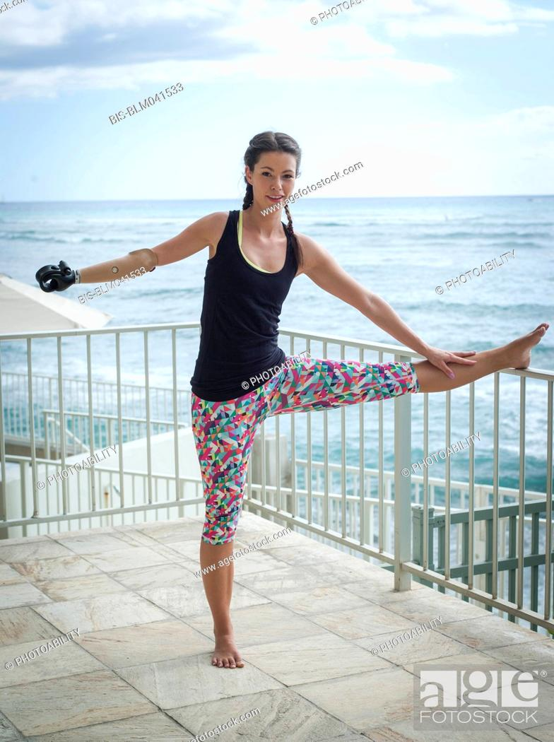 Imagen: Mixed race amputee athlete stretching on balcony.