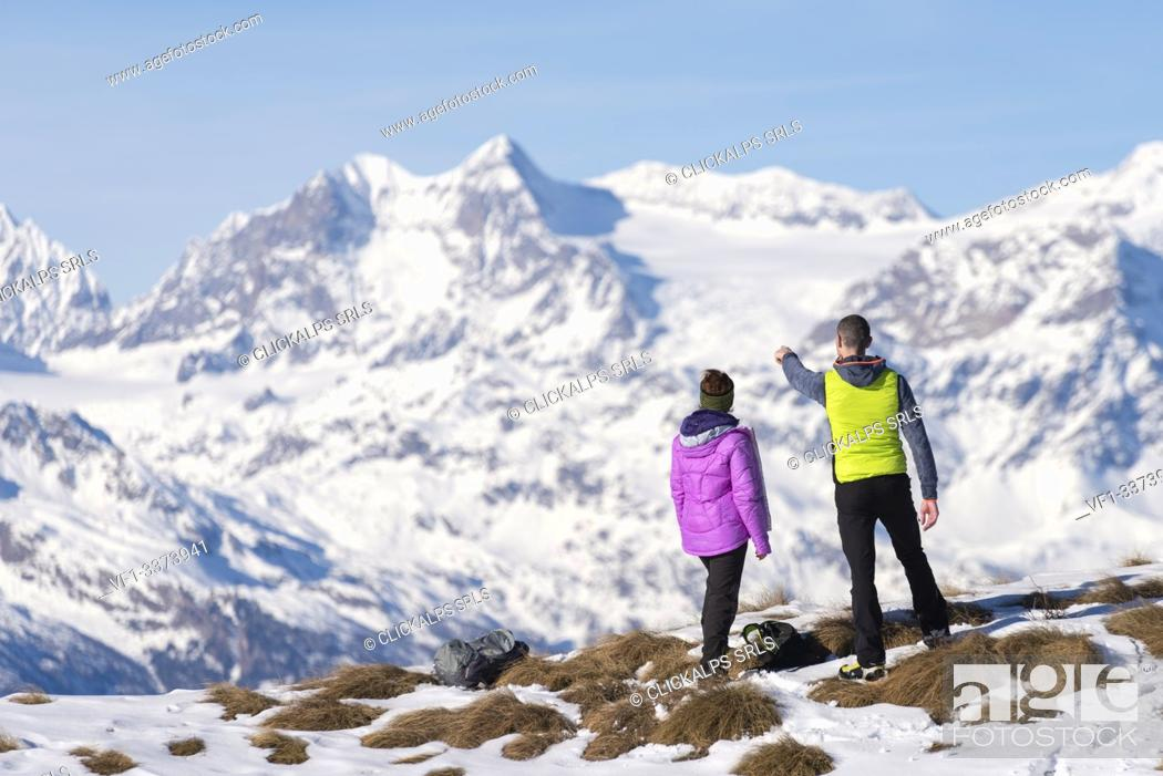 Stock Photo: .Couple of hikers admire the Swiss mountains from Monte Padrio, Corteno Golgi, Province of Brescia, Lombardy, Italy, Europe.