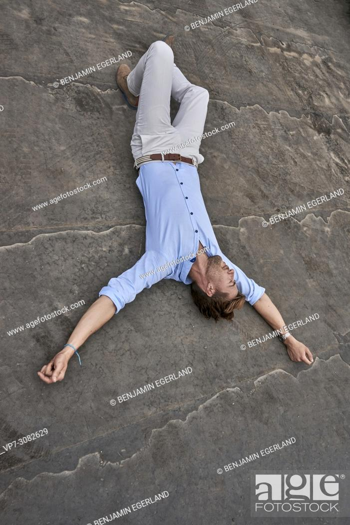 Stock Photo: business man lying on street, exhausted, blogger Axel Sprenger, in Munich, Germany.