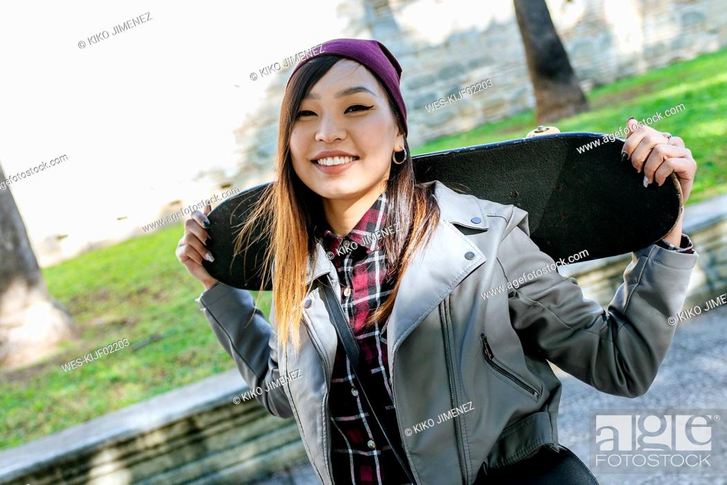Photo de stock: Portrait of smiling young woman with skateboard on her shoulders.