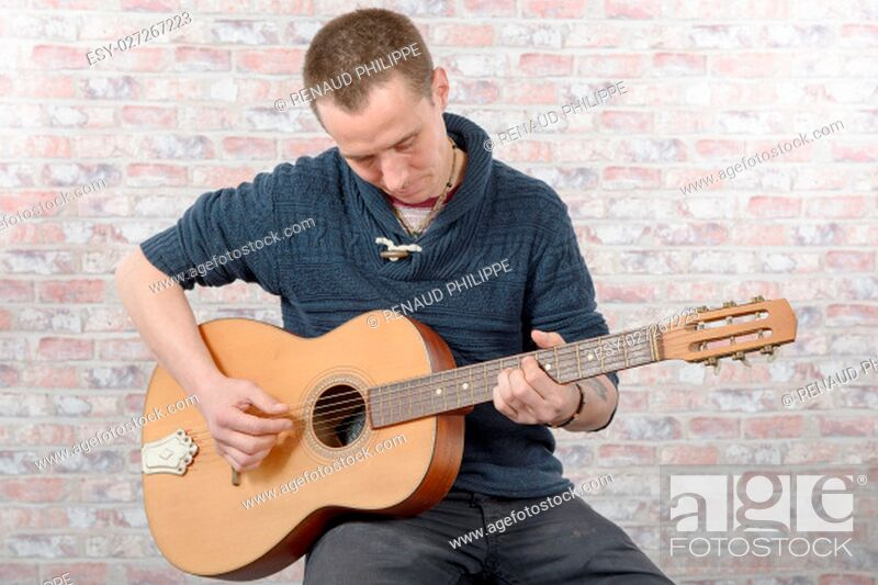 Stock Photo: young man with an acoustic guitar in his hands.