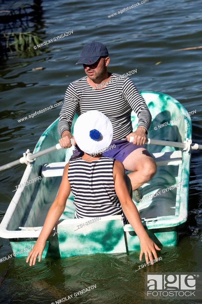 Stock Photo: Russian Federation. Belgorod region. A man with a boy in a striped vest on boat trips.