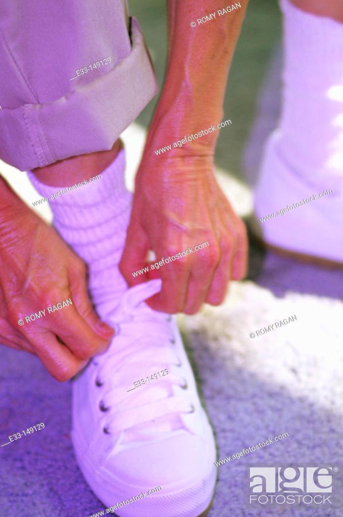 Stock Photo: Senior woman tying shoelace.