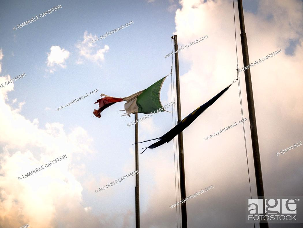 Stock Photo: Italian and European flags snatched by the wind.